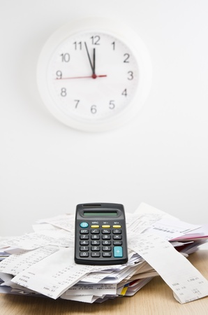 Tax time. Calculator on top of a stack of bills with a clock behind