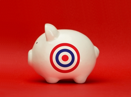 Savings on target. White piggy bank with a bullseye target printed on it
