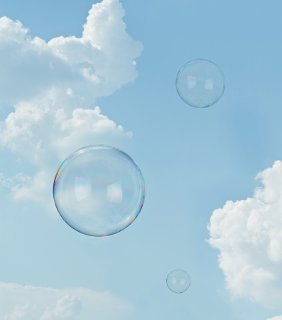 levitation: Floating soap bubbles against clear sunlit blue sky and clouds