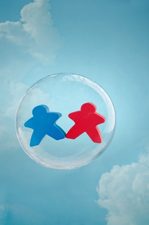 Love is in the air. Couple figurines  floating in a soap bubble in the sky photo