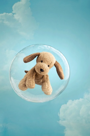 Childhood dreaming. Cute puppy toy floating in a soap bubble in the sky photo