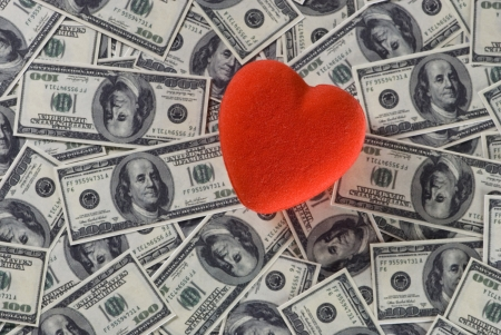 holiday profits: Red heart on us dollar bills  background