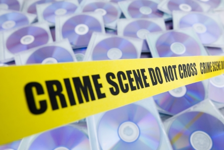 information technology law: Lots of pirated compact disks enclosed by police tape Stock Photo