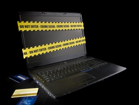 Laptop wrapped in police tape on black background photo