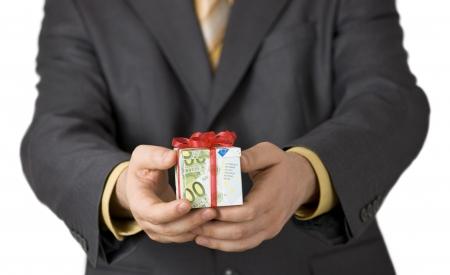 Uomo che offre un aiuto finanziario in una scatola regalo avvolto in banconote euro