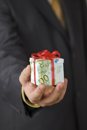 profit celebration: Man offering an expensive gift box wrapped in euro banknotes Stock Photo