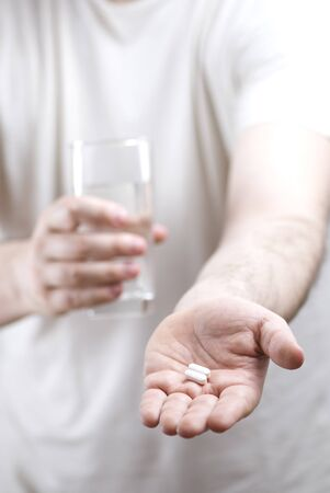Close-up of a person offering pills and a glass of water photo