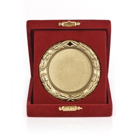 Golden medal in a red velvet box on white background photo