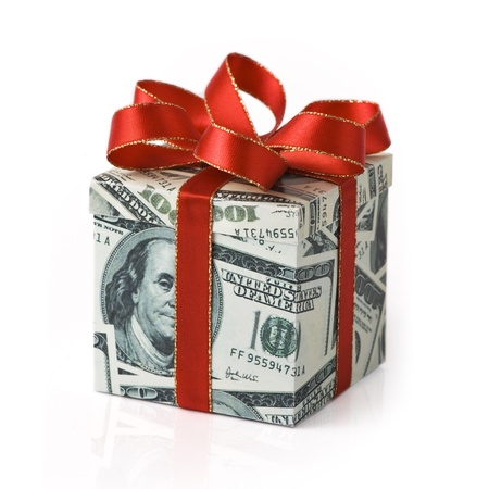 A gift box covered in US money with red colored ribbon applied