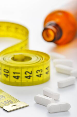 Measuring tape and pills for dieting concept