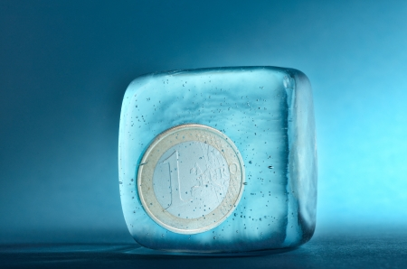 One euro coin frozen in ice cube Stock Photo