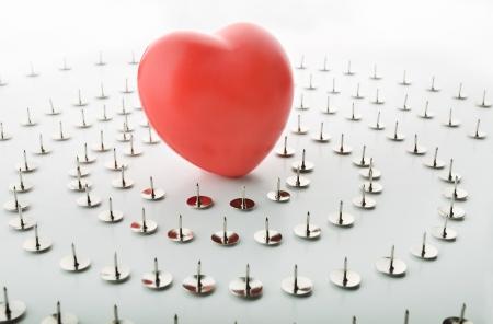 confined: Heart surrounded by thumbtacks symbolizing solitude