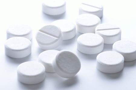 aspirin: Close-up of white pills spilled on white background Stock Photo