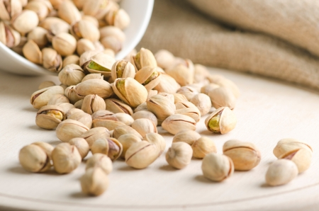 pistachios: Pistachio nuts just falling on a wooden board Stock Photo