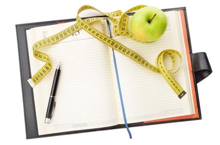 Taccuino e penna con mela e nastro di misurazione per la scrittura delle note di dieta