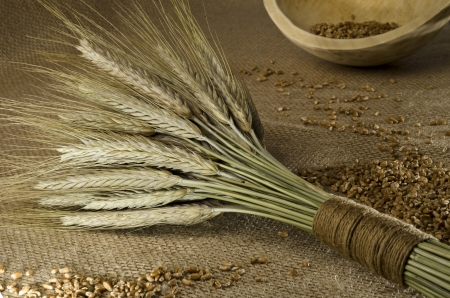 Rustic setting with wheat sheaf and grains photo