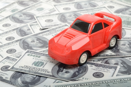car gas: Red car over a lot of dollar bills