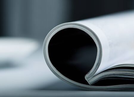 Rolled glossy magazine on a table with very shallow depth of field  photo