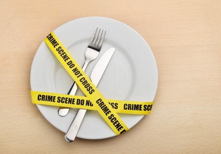 Cibo pericoloso. Piatto vuoto, forchetta e coltello avvolto in nastro di crimine scena. Archivio Fotografico