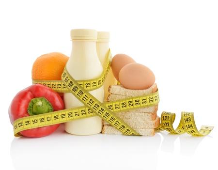 metro de medir: Una alimentación saludable o el concepto de dieta. Alimentos envuelto en cinta de medición.
