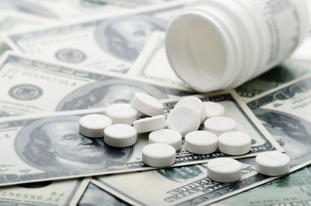 suggesting: Pill bottle on a pile of hundred dollar bills suggesting the high cost of healthcare