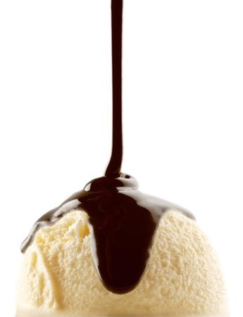 バニラアイス クリームのスクープを介して注がれているチョコレート シロップ