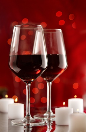 Two glasses of red wine and candles with celebratory lights