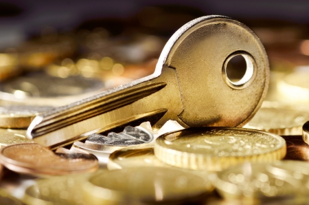 Close-up of a key on top of a pile of golden coins