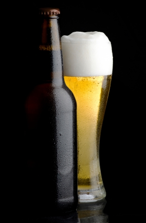 draught: Beer bottle and glass of cold beer on black background