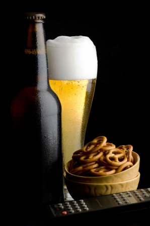 pretzels: Pretzels with beer and remote control on black background