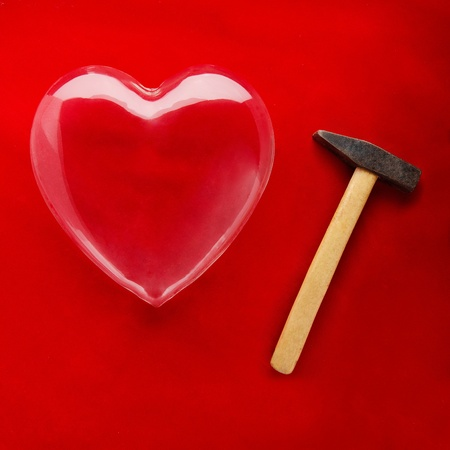 fragility: A glass heart and a hammer ready to break it symbolising fragility