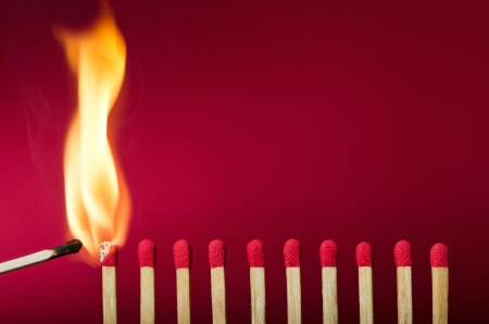 domino: Burning match setting fire to its neighbors, a metaphor for ideas and inspiration Stock Photo