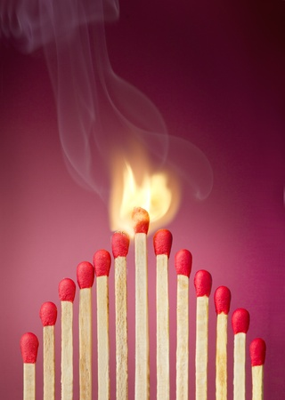 adulation: Burning match setting fire to its neighbors, a metaphor for ideas and inspiration Stock Photo
