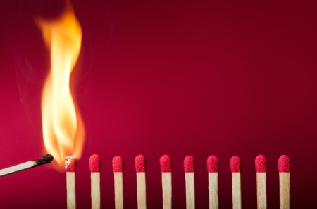 Burning match setting fire to its neighbors, a metaphor for ideas and inspiration Stock Photo