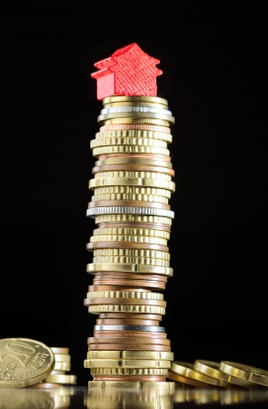 house prices: Model house on a stack of coins representing high prices on real estate market