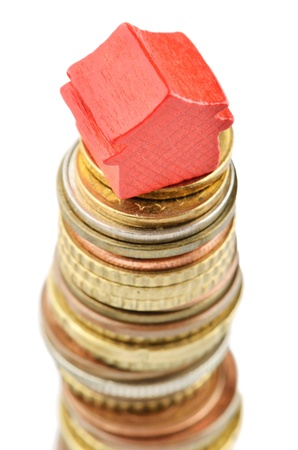 subprime mortgage crisis: House on gold coins increasing in value Stock Photo