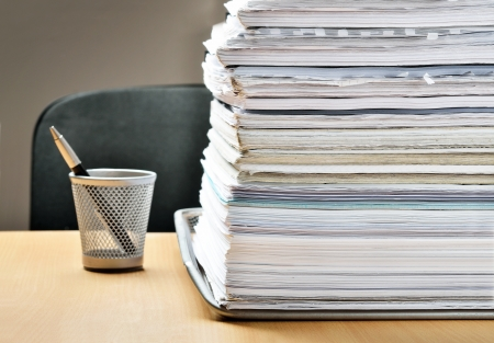 A huge pile of paperwork on a desk