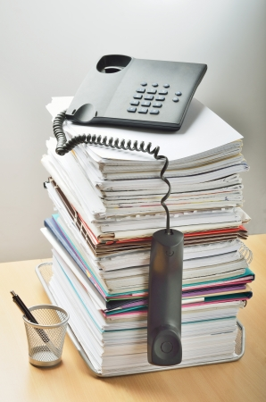 A huge pile of paperwork on a desk and a phone above it photo