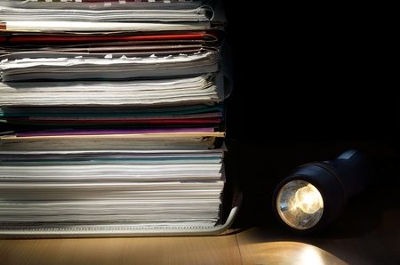 intellectual property: A stack of papers and a flashnight on a desk in a low light scene Stock Photo