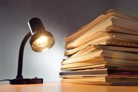 gestion documental: Trabajando hasta tarde, la lámpara y el papeleo apilados en un escritorio