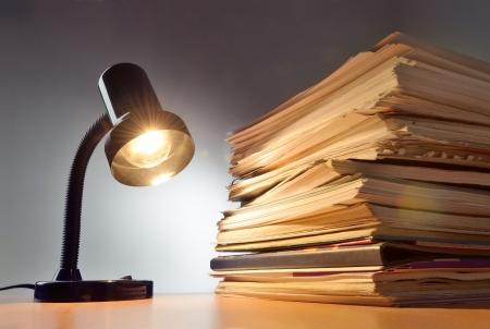 crisis management: Working late, lamp and paperwork stacked on a desk Stock Photo