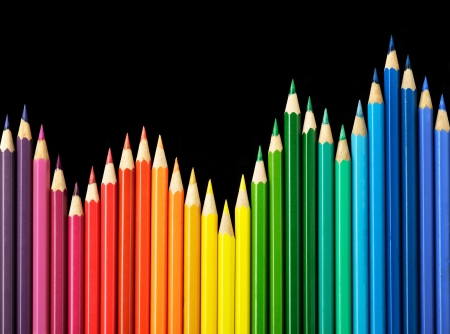 art and craft equipment: Colored pencils arrangement on black background