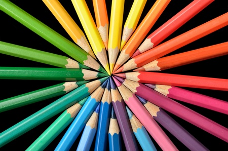 Circular arrangement of colored pencils on black background photo