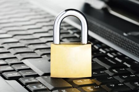 Padlock on notebook keyboard, symbolising computer related security photo