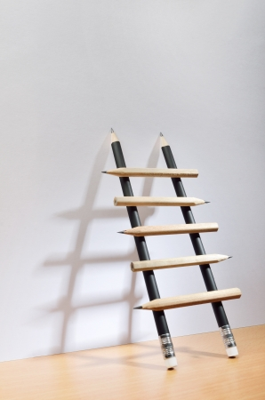 Pencil ladder leaning against white wall with copy space Stock Photo