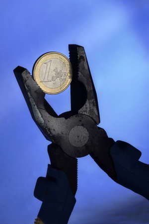 economic depression: Euro coin and pliers symbolizing the European Union economic depression and the European currency under pressure