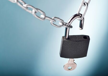 Unlocking a padlock securing two metal chains with blue background photo