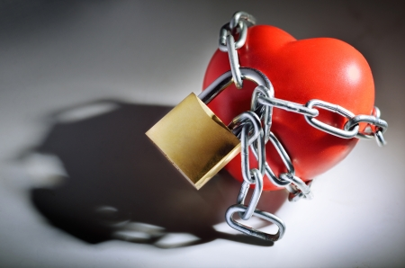 Heart wrapped in chains symbol of solitude Stock Photo
