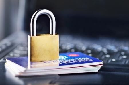 personalausweis: Vorh�ngeschloss und Stapel von Kreditkarten auf der Oberseite des Laptops
