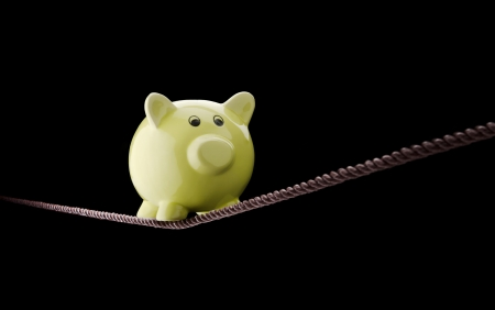 budget crisis: Piggy bank balancing on tightrope